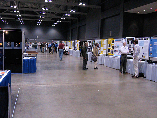A long shot of the poster hall, including people looking at several posters
